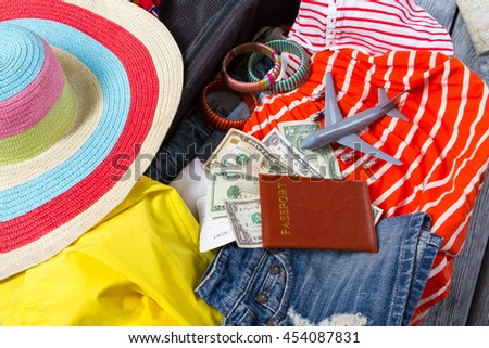 Passport with dollars on clothes. Striped bracelets and beach hat. Go travelling this summer. Personal document and plane ticket. - stock photo