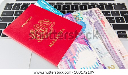 Passport with Hong Kong dollars and airplane boarding pass on a laptop