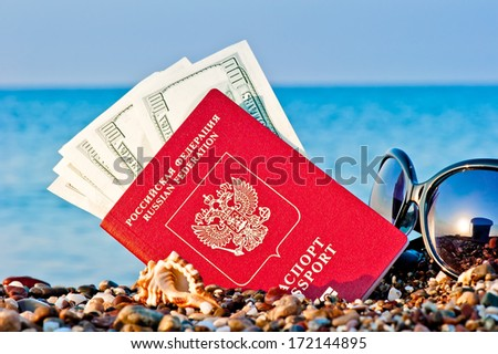 passport with money and sunglasses on the beach  - stock photo