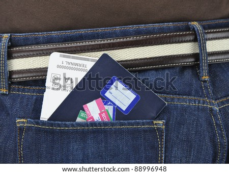 Passport with Security Stickers Airline Boarding Pass Ticket Receipt in pock of Denim Blue Jean Pans of Person - stock photo