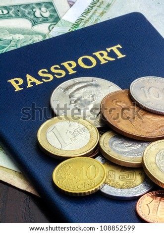 Passport with world currency. Blue passport with world currency on dark wood table - stock photo