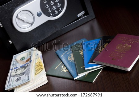 Passports and money - multi national ID, Seaman's Books, miscellaneous currency banknotes  - spy / agent concept / Intelligence Secret Service - stock photo