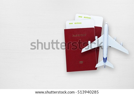 Passports, boarding passes and toy airplane on white table