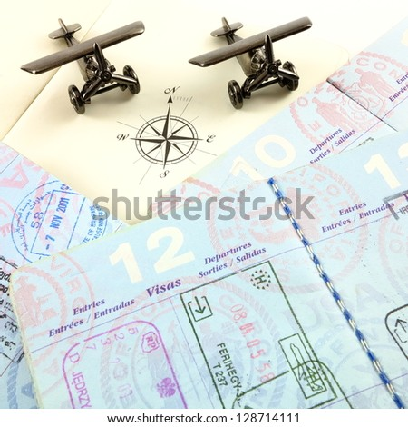 Passports, compass rose from an atlas and toy airplanes - stock photo