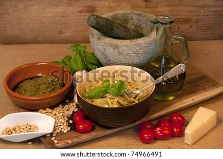 Pasta and all the ingredients to make Italian home made pesto in a rustic way. - stock photo