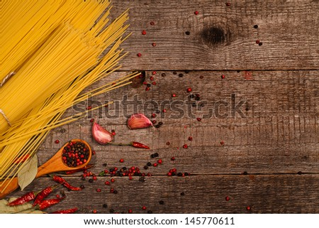 pasta and cooking ingredients on wooden table - stock photo