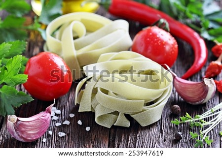 Pasta and fresh vegetables on a rustic wooden table.Selective focus. - stock photo