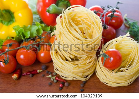 Pasta and fresh vegetables on a wooden table