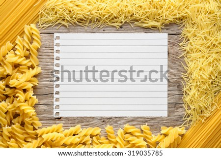 Pasta and paper for recipe on wooden background - stock photo
