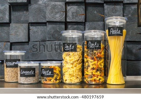 Pasta and spices in jars on a shelf in the kitchen