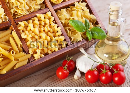 Pasta assortment and fresh seasoning ingredients on old wooden table - stock photo