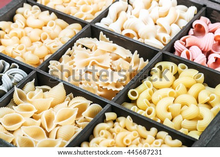 pasta assortment background. Pasta in a wooden box. Italian pasta of different colors - stock photo