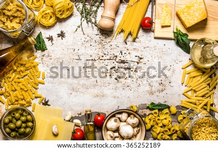 Pasta background. Dry pasta with vegetables, mushrooms, cheese and herbs. On rustic background.  Free space for text . Top view - stock photo