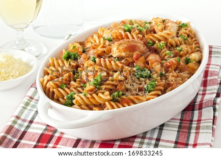 Pasta Bake with Chicken - fusili or spiral pasta, baked with chicken and marinara, topped with green chilli and parmesan. - stock photo