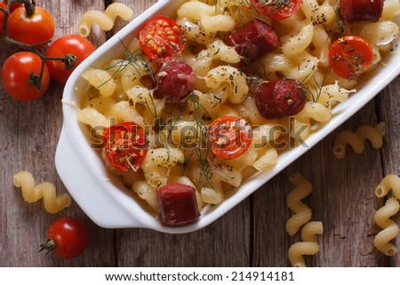 pasta baked with cherry tomatoes and sausages closeup and ingredients top view. horizontal  - stock photo