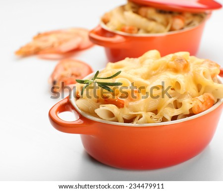 Pasta baked with shrimps and cheese in ceramic pot