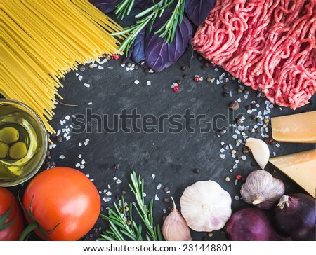 Pasta Bolognese ingredients: spaghetti, minced meat, tomatoes, basil, rosemary, parmesan cheese, olive oil, garlic, onon, sea salt and spices on a dark stone background with a copy space in the center - stock photo