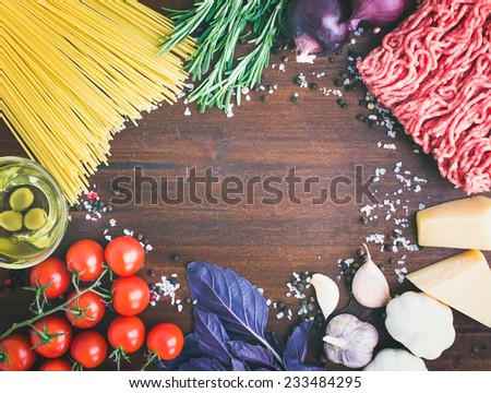 Pasta Bolognese ingredients: spaghetti, minced meat, tomatoes, basil, rosemary, parmesan, olive oil, garlic, onion, sea salt and spices on a dark wooden background with a copy space in the center - stock photo