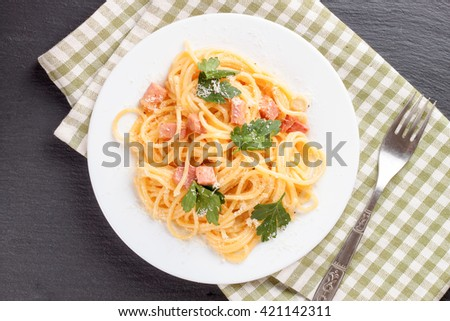 Pasta Carbonara with ham and cheese on checkered towel. Top view. - stock photo
