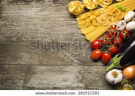 Pasta collection with fresh ingredients on wooden background