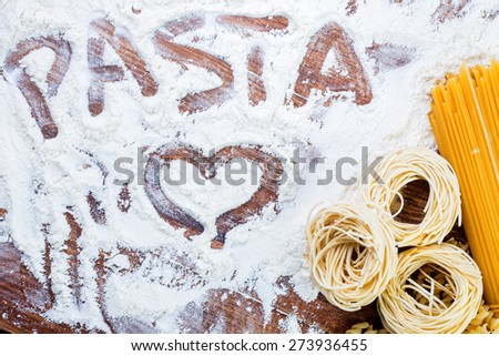 Pasta composition with pasta text and heart written flour on wooden rustic table top view