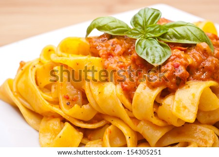 Pasta decorated with basil leaves. White plate on wooden table  - stock photo