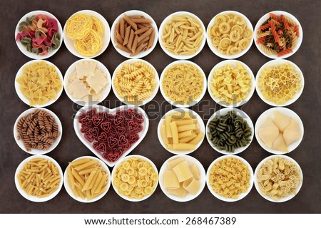 Pasta dried food selection in white porcelain bowls over lokta paper background.. - stock photo