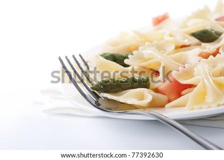 Pasta farfalle, tomato and asparagus salad on white background - stock photo