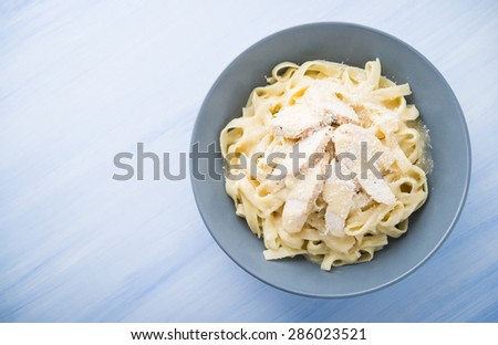 Pasta fettuccine alfredo with chicken and parmesan on blue wooden background top view. Italian cuisine. Space for text. - stock photo