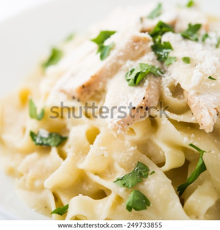 Pasta fettuccine alfredo with chicken, parmesan and parsley on white background close up. Italian cuisine. - stock photo
