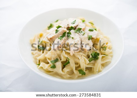 Pasta fettuccine alfredo with chicken, parmesan and parsley on white background. Italian cuisine. - stock photo