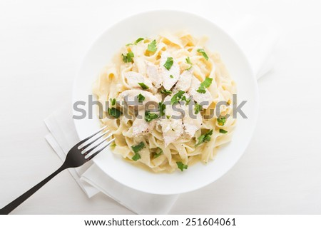 Pasta fettuccine alfredo with chicken, parmesan and parsley on white background top view. Italian cuisine. - stock photo