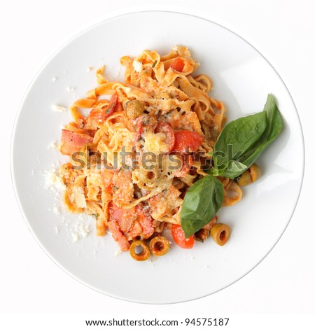 Pasta fettuccine with tomato, olives and bacon on white round dish isolated on a white background. Top view. - stock photo