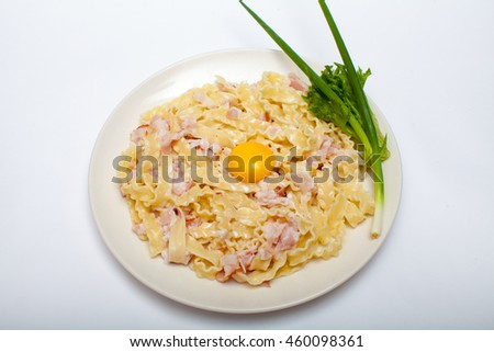 Pasta. Food. Carbonara. Italian food. Yolk. The food in the restaurant. Menu. Ham. Egg. Cream. Tasty. Appetizing feed. On a white background. White tablecloth. Served table in an Italian restaurant.