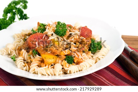 Pasta Fusilli & Bolognese style meat sauce with added vegetables & grated Italian Parmigiano Reggiano.  - stock photo
