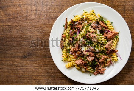 pasta fusilli salad with tuna and onion in white plate on a wooden background. with copy space. top view