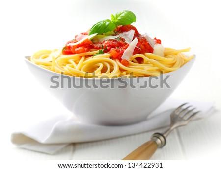 Pasta in a white bowl with tomato sauce and fresh basil set against a white napkin on a white table. - stock photo
