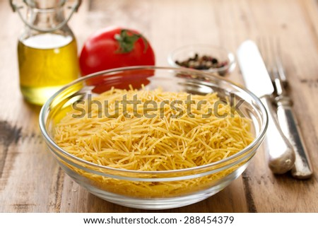 pasta in bowl with oil and tomato - stock photo