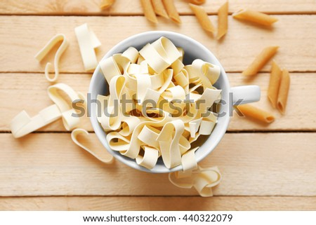 Pasta  in cup on wooden table background