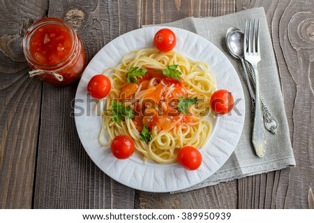 Pasta in tomato sauce with tomatoes and greens on a wooden background. Top view.