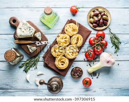 Pasta ingredients. Cherry-tomatoes, spaghetti pasta, rosemary and spices on the wooden table. - stock photo