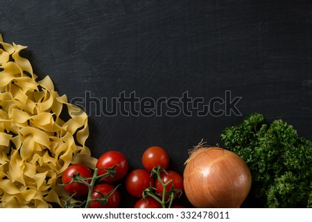Pasta ingredients on dark background - stock photo