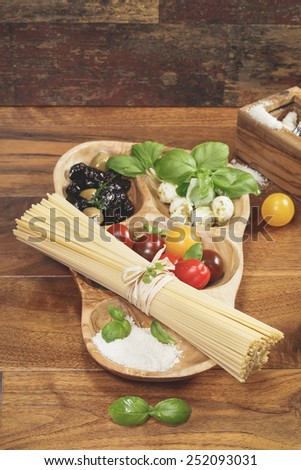 Pasta Ingredients.Pasta spaghetti with tomatoes, olives, mozzarella and Parmesan cheese and basil. Ingredients for cooking over rustic table. A macro photograph with  shallow depth of field - stock photo