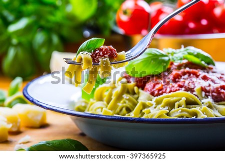 Pasta. Italian and Mediterranean cuisine. Pasta Fettuccine with tomato sauce basil leaves garlic and parmesan cheese. An old home kitchen with old kitchen utensils. Portion of on a fork. - stock photo