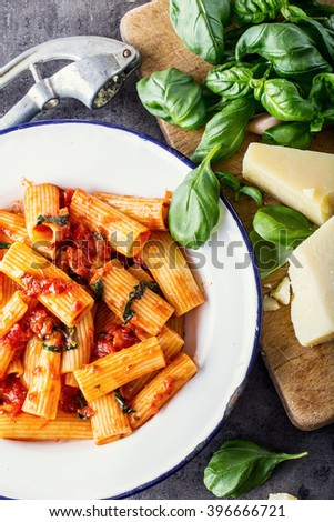 Pasta. Italian and Mediterranean cuisine. Pasta Rigatoni with tomato sauce basil leaves garlic and parmesan cheese. An old home kitchen with old kitchen utensils. - stock photo