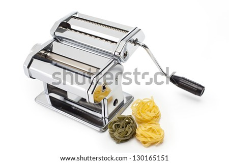 Pasta machine with fresh noodles isolated on white - stock photo