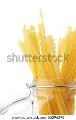 Pasta (mafaldi) in glass jar isolated on white background.