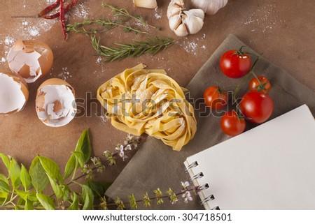 Pasta menu, Preparation of pasta recipe ingredients with empty notebook - stock photo