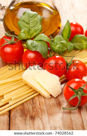 pasta, olive oil and tomatoes on the wood background