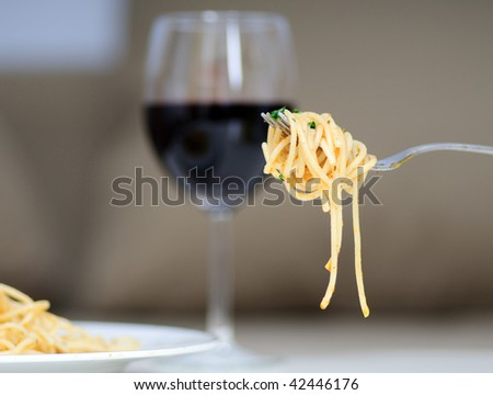 Pasta on a fork with plate and a glass of red wine. Focus on fork with pasta